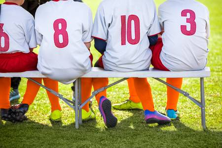 76746690-soccer-team-kids-sitting-on-the-bench-children-in-white-shirts-with-soccer-numbers-and-orange-tights